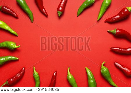 Frame Made Of Hot Red And Green Fresh Chili Peppers On Red Background Flat Lay Top View. Seasoning F