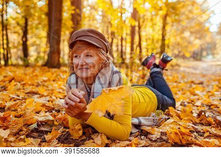 Fall Activities. Woman Lying On Heap Of Leaves In Autumn Park. Senior Woman Having Fun Outdoors
