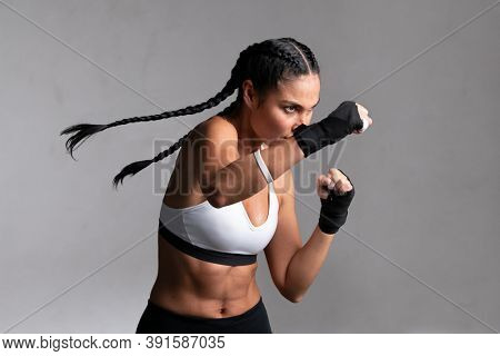 Determined middle aged woman boxer preparing for boxing fight. Fitness mid adult woman preparing for boxing training at gym. Beautiful strong sportswoman in boxing gloves prepared right hand punch.