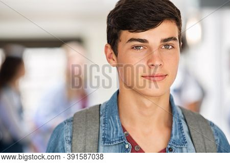 Portrait of handsome high school student standing in school hallway and looking at camera. Intelligent college guy with backpack smiling with copy space. Confident university young man in campus.