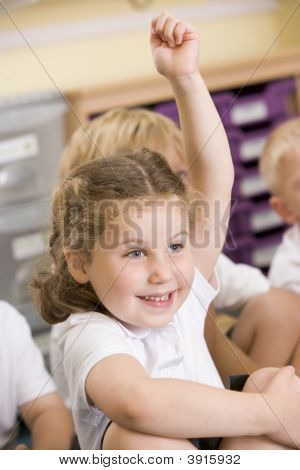 Portrait Of Child Sitting On Carpet In Classroom