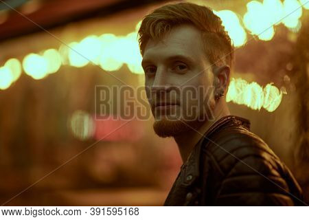 Night life in a big city. Modern young man walks along a city street lit by night lights.