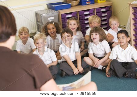 Teacher Reading Book To Children Sat On Carpet