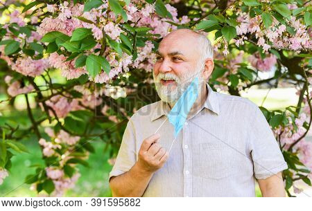 Asthma Treatment Concept. Pollen Allergen. Man And Flowers. Respiratory Condition. Difficulty In Bre
