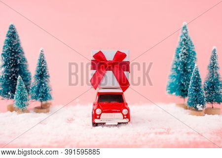 Miniature Red Car Toy Delivering Gift Box And Christmas Tree On Pink Background. Christmas Greeting