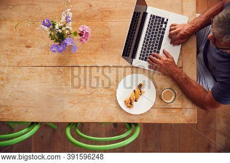 Overhead View Of Mature Man Working On Laptop In Coffee Shop