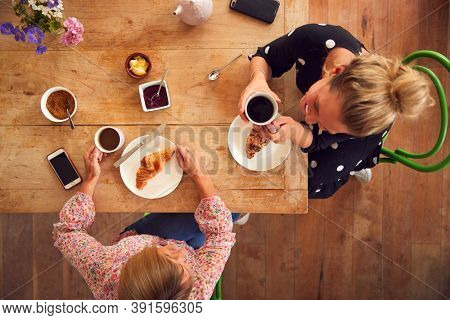 Overhead View Of Two Female Friends In Coffee Shop Meeting Up In Socially Distanced Way