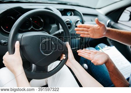 Female Hands Hold Steering Wheel. Male Instructor Demonstrates With His Hand What To Do With A Wheel