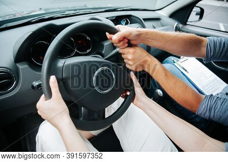 Two Pairs Of Hands Turn Steering Wheel Together. Female Student At Driving Courses Hold The Wheel An