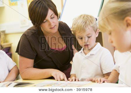 Teacher Helping Children To Read