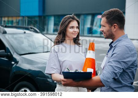 Female Student Of Driving School Signs Instructors Papers And Looks At Him With Interest. Orange Tra