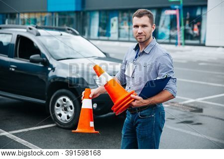 Driving Instructor Loves His Job. Young Attractive Man Standing With Clipboard And Cones In His Hand
