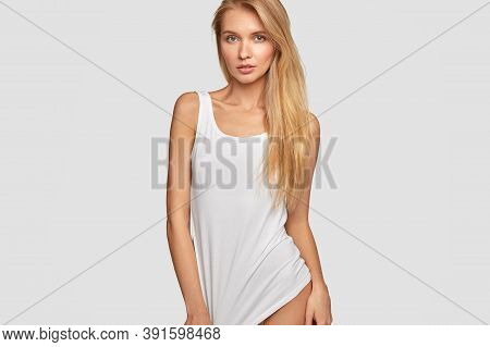 Cropped Image Of Serious Light Haired Woman Wears Casual Oversized T Shirt, Models In Studio For Fas