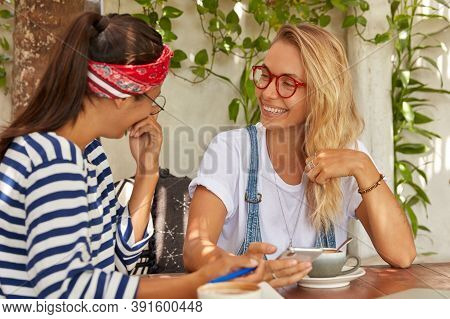 Glad Mixed Race Two Women Have Funny Expressions, Laugh Happily While Remember Some Moment From Thei