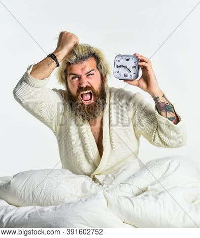 Self Discipline Concept. Exhausted Man Being Awakened By Alarm Clock In Bedroom. Mature Man On Bed T