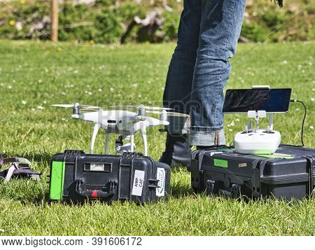 Jumieges, France - June Circa, 2019. Mature Male Technicians Outdoor, On Grass, Using Professional D