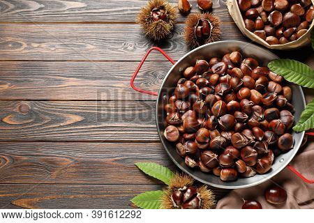 Delicious Roasted Edible Chestnuts On Brown Wooden Table, Flat Lay. Space For Text
