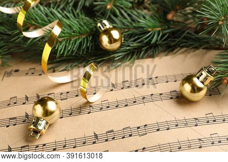 Fir Branches, Golden Streamer And Balls On Christmas Music Sheets, Closeup