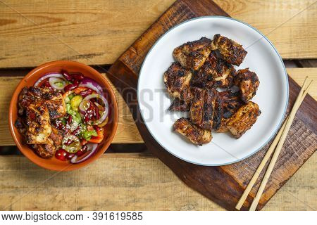 Plates Of Pan-asian Salad With Sesame Seeds And Grilled Chicken In Yakitori Sauce On Wooden Stands A