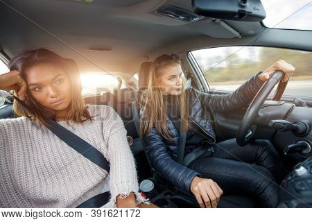Two Young Girls Travelling By Car At Sunny Morning