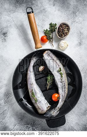 Raw Pollock Fish In A Pan. Organic Seafood. Gray Background. Top View