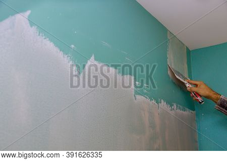 Professional Builder Smooths Wall With Spatula Putty Put On Leveled Surface Of Wall Repair In Own Ap