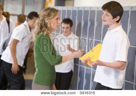Teen Boy Being Told Off By Teacher In School Corridor