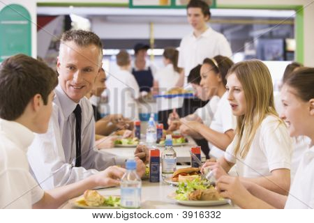 Teen Pupils And Teacher In School Canteen On Lunch Break