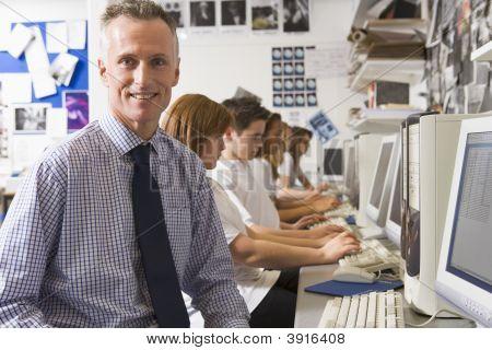 Teacher Helping Teen Pupils Study On School Computers