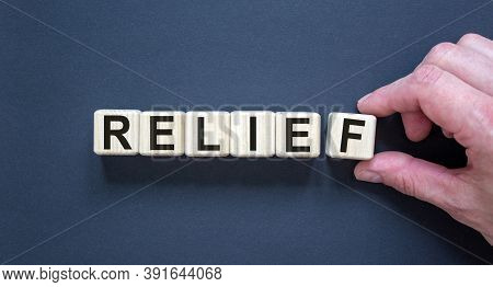 Wood Cubes With Word 'relief' On Paper Black Background, Copy Space. Male Hand. Business Concept Suc