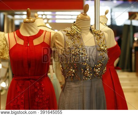 Female Mannequins In Beautiful Red And Gray Festive Dresses With Golden Decor At Indian Clothing Sto