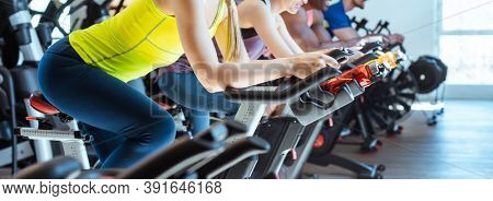 Very fit Caucasian woman and her friends on fitness bike in gym