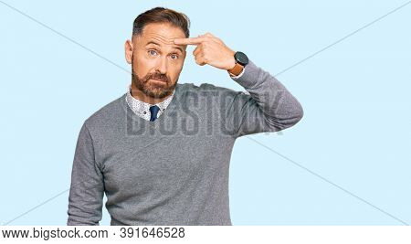 Handsome middle age man wearing business clothes pointing unhappy to pimple on forehead, ugly infection of blackhead. acne and skin problem