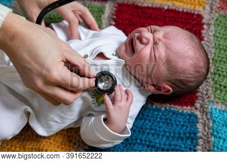 Portrait Of Newborn Baby Crying While Suffering From Illness And Selective Focus Of Hands Of Young F