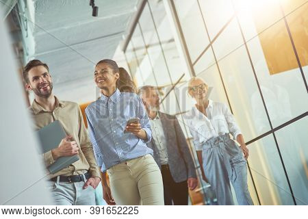 Two Young Happy Diverse Male And Female Coworkers Discussing Something And Smiling While Walking Wit