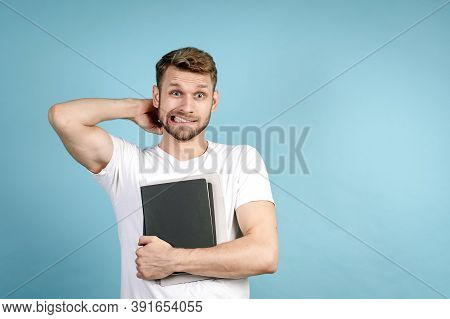 Oops, Thats The Problem. Portrait Of Confused Adult Guy In White T-shirt Holding Copybooks With Home