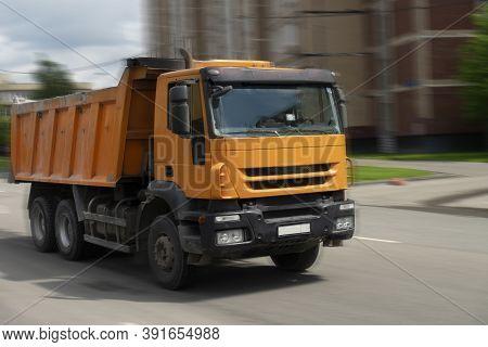 Orange Dump Truck Rides On The Road To Work