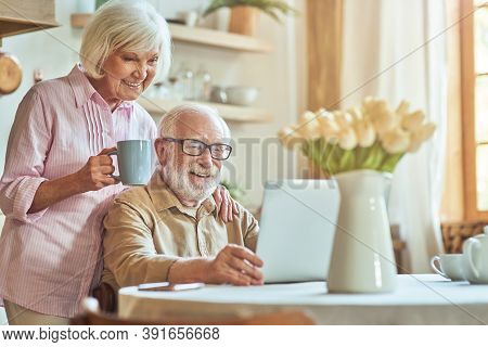 Happy Elderly Couple Using Laptop While Spending Morning Together At The Kitchen