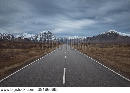 The Road Leading To The Snow-capped Mountains Through The Valley. Scottish Highlands Of Glen Coe. Sc
