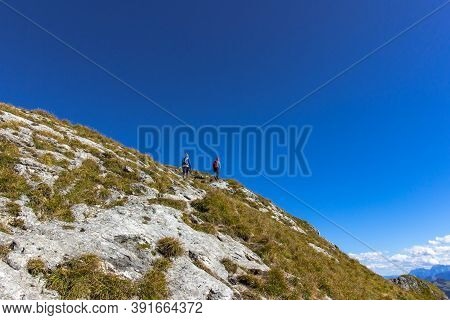 Active Girls Hiking To The Peak Of Alps, Austria. Successful Female Backpackers Enjoying Their Adven
