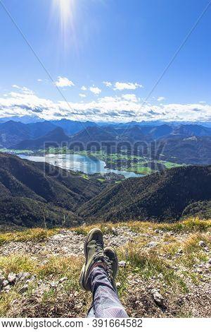 Legs Of Traveler Sitting On A High Mountain. Freedom Wanderlust Travel Concept. Trekking Boots Again