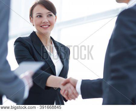 Businesswoman shaking hands with a businssman during a meeting