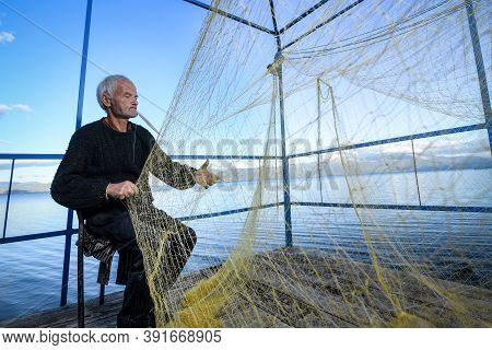Senior Fisherman Holding Fishing Net Near The Beach. Fisherman Hands Close Up. A Fisherman Preparing
