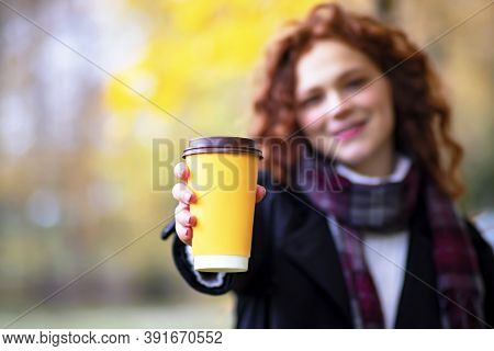 Ginger Woman Holds Out A Glass Of Coffee To Go, The Concept Of Vigor, Morning, Romance And A Walk.