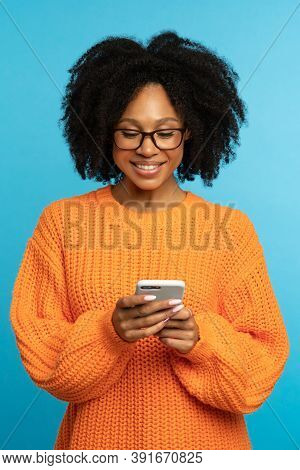 Stylish Happy Dark Skinned Millennial Woman With Curly Hair Wear Orange Knitted Jumper, Reading Mess