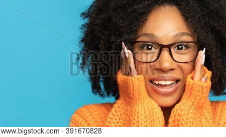Surprise Biracial Woman In Orange Jumper Surprise Holding Cheeks By Hands. Mixed Race Woman Wear Gla