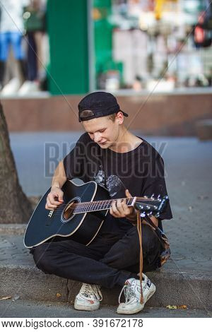 Nickolaev, Ukraine - August 30, 2020:  Street Musician Sitting On The Road And Playing Guitar In The
