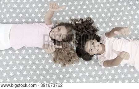 Kids Show Thumbs Up Gesture. Girls Children On Bed Top View. Pajamas Party Concept. Girls Just Want