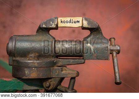 Concept Of Dealing With Problem. Vice Grip Tool Squeezing A Plank With The Word Hoodlum