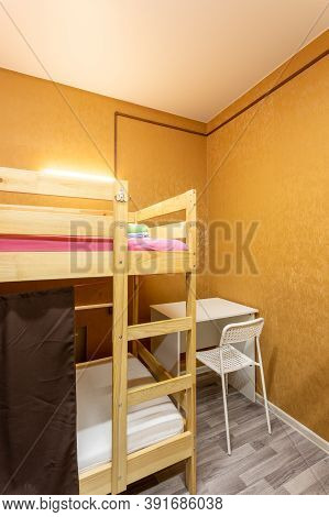 Wooden Bunk Bed With Curtains, Desk And Chair In Large Hostel Dorm Room